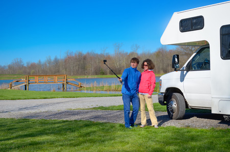 Family vacation, RV travel, happy couple making selfie in front of camper on holiday trip in motorhome