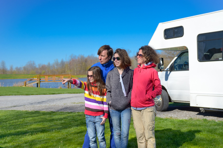 Family vacation, RV travel with kids, happy parents with children have fun on holiday trip in motorhome, camper exterior photo