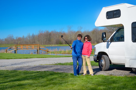 Family vacation, RV travel, happy couple making selfie in front of camper on holiday trip in motorhome photo