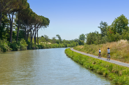 Family on bikes, mother and daughter cycling by canal du Midi, active summer vacation in France photo