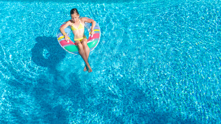 Aerial view of girl in swimming pool from above, kid swim on inflatable ring donut and has fun in water on family vacation photo
