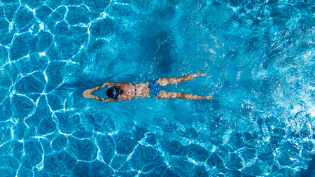 Aerial top view of woman in swimming pool water from above, tropical vacation holaday concept photo