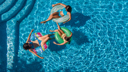 Aerial top view of family in swimming pool from above, mother and kids swim and have fun in water on family vacation in hotel resort photo
