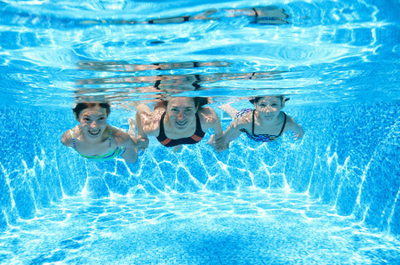 Family swims in pool under water, happy active mother and children have fun underwater, fitness and sport with kids on summer vacation photo