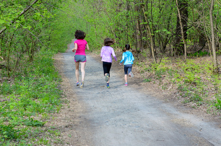 Family fitness and sport, happy active mother and kids jogging outdoors, running in forest photo