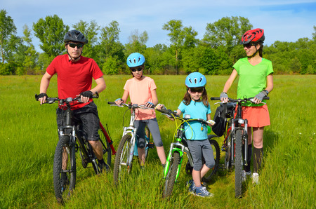 Family on bikes outdoors, happy active parents and two kids cycling outdoors on spring meadow, fitness and healthy lifestyle concept photo