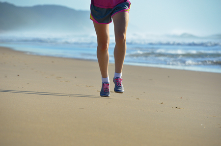 Fitness and running on beach, woman runner legs in shoes jogging on sand near sea, healthy lifestyle and sport concept photo