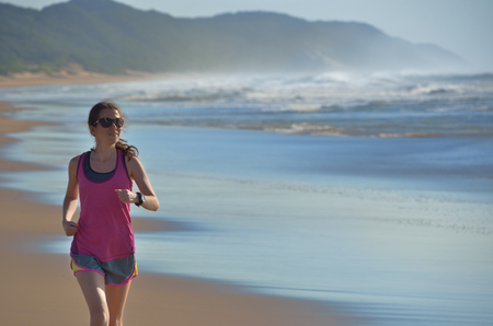 Fitness and running on beach, happy woman runner jogging on sand near sea, healthy lifestyle and sport concept photo