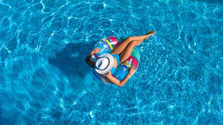 Lucht bovenaanzicht van een mooi meisje in het zwembad van bovenaf, ontspan zwemmen op opblaasbare ring donut en heeft plezier in water op familie vakantie