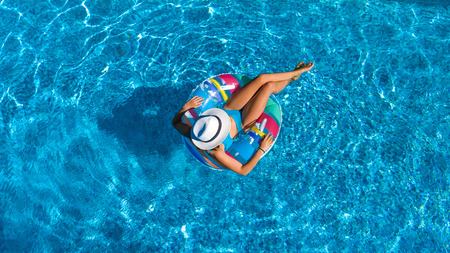 Vista aerea superiore di bella ragazza in piscina da sopra, rilassarsi nuotare sulla donut gonfiabile anello e divertirsi in acqua in vacanza in famiglia Archivio Fotografico - 86038448