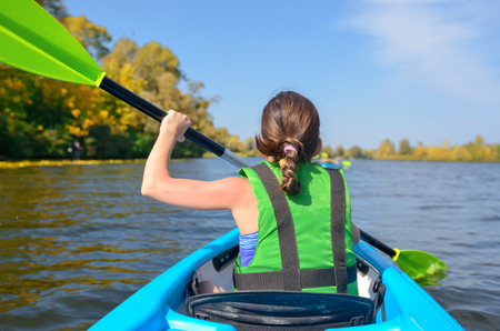 Family kayaking, child paddling in kayak on river canoe tour, kid on active summer weekend and vacation, sport and fitness concept