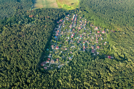 Aerial top view of residential area summer houses in green forest from above, countryside real estate and small dacha village in Ukraine