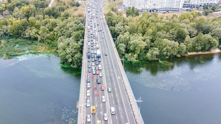 Aerial top view of bridge road automobile traffic jam of many cars from above, block and road repair, city transportation concept, Kyiv