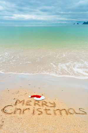 Christmas holiday vacation concept, Merry Christmas written on tropical beach sand background Stock Photo