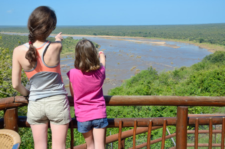 Family safari vacation in South Africa, mother and daughter looking at beautiful african river view, tourists travel Kruger national park, South Africa