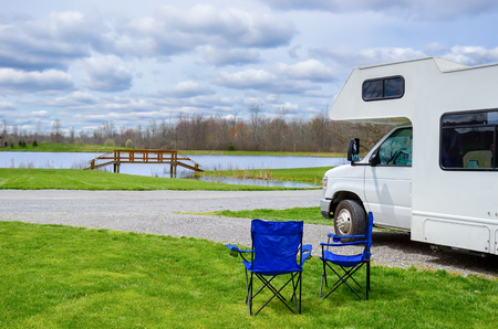 RV (camper) and chairs in camping, family vacation travel, holiday trip in motorhome Stock Photo