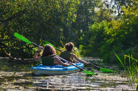 Familie kajakend moeder en kind die in kajak op de reis van de de rivierreis actief herfstweekend en vakantiesport en fitness concept paddelen Stockfoto