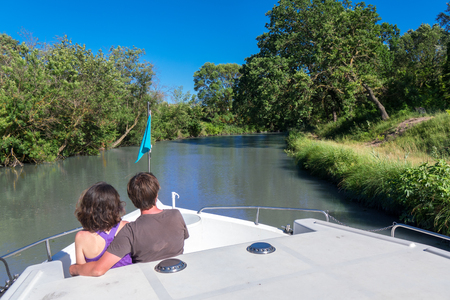 Romantic vacation, holiday travel on barge boat in canal, happy couple having fun on river cruise in houseboat