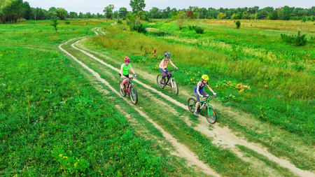 Family cycling on bikes outdoors aerial view from above, happy active mother with children have fun, family sport and fitness Reklamní fotografie