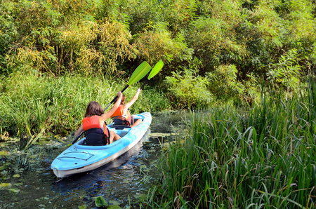 Family kayaking, mother and child paddling in kayak on river canoe tour having fun, active autumn weekend and vacation, fitness concept