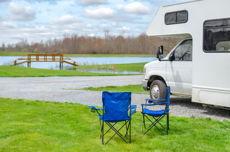 RV camper and chairs in camping, family vacation travel, holiday trip in motorhome Reklamní fotografie