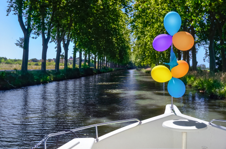 Vacation boat with balloons in Canal du Midi, family travel river cruise by barge penichette, holidays in Southern France