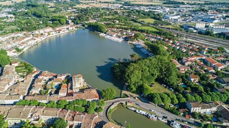 Aerial top view of Castelnaudary residential area houses roofs, streets and canal with boats from above, old medieval town background, France