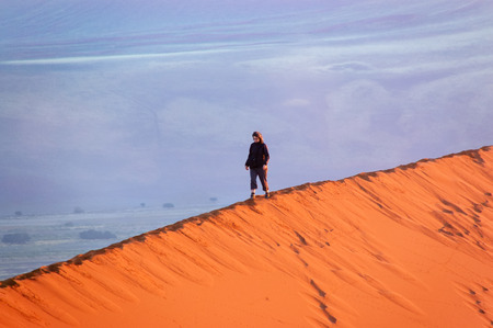 Woman tourist walking on top of dune in Namib desert, holiday travel in Africa, Namibia adventure