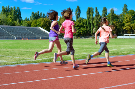 Family sport and fitness, happy mother and kids running on stadium track outdoors, children healthy active lifestyle concept Foto de archivo