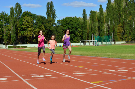 Family sport and fitness, happy mother and kids running on stadium track outdoors, children healthy active lifestyle concept Reklamní fotografie