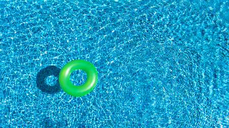Aerial view of colorful inflatable ring donut toy in swimming pool water from above, family vacation holiday resort background