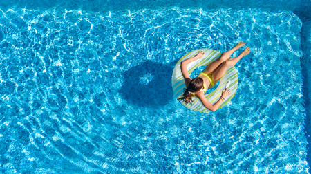 Aerial top view of little girl in swimming pool from above, kid swims on inflatable ring donut , child has fun in water on family vacation resort Reklamní fotografie - 97012848
