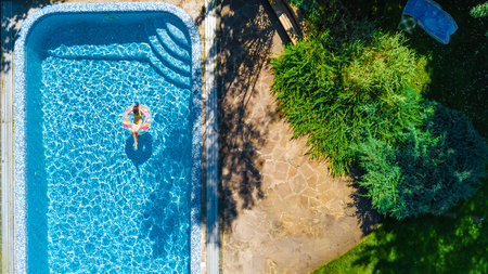 Aerial top view of little girl in swimming pool from above, kid swims on inflatable ring donut , child has fun in water on family vacation resort