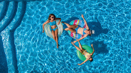 Aerial top view of family in swimming pool from above, happy mother and kids swim on inflatable ring donuts and have fun in water on family vacation, tropical holidays on resort Reklamní fotografie - 97268151