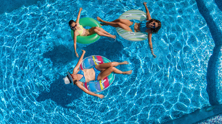 Aerial top view of family in swimming pool from above, happy mother and kids swim on inflatable ring donuts and have fun in water on family vacation, tropical holidays on resort Reklamní fotografie - 96999376