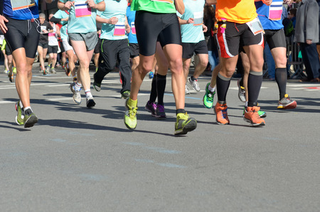 Marathon running race, many runners feet on road racing, sport competition, fitness and healthy lifestyle concept