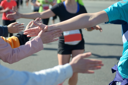 Marathon running race, support runners on road, childs hand giving highfive, sport concept