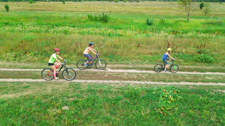 Family cycling on bikes outdoors aerial view from above, happy active mother with children have fun, family sport and fitness Reklamní fotografie - 101497016