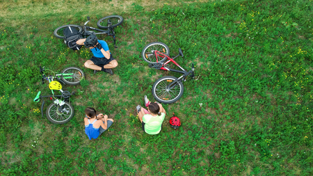 Family cycling on bikes outdoors aerial view from above, happy active parents with child have fun and relax on grass, family sport and fitness on weekend Reklamní fotografie - 101497014
