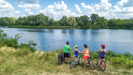 Family on bikes cycling outdoors, active parents and kids on bicycles, aerial view of happy family with children relaxing near beautiful river from above, sport and fitness concept Reklamní fotografie