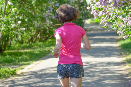Woman runner jogging in spring park with lilac blossom, morning run outdoors, fitness and running healthy lifestyle concept