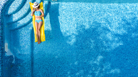 Beautiful young girl relaxing in swimming pool, swims on inflatable mattress and has fun in water on family vacation, tropical holiday resort, aerial top view from above