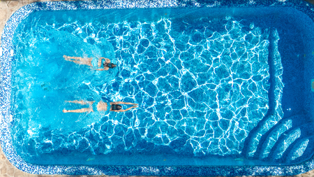 Aerial drone view of girls in swimming pool water from above, active children swim, kids have fun on tropical family vacation, holiday resort concept Reklamní fotografie