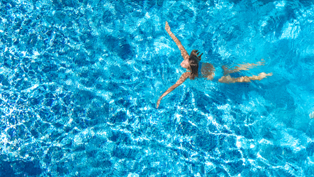 Aerial drone view of active woman in swimming pool from above, girl swims in blue water, tropical vacation, holiday on resort concept