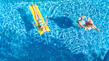 Aerial drone view of children in swimming pool from above, happy kids swim on inflatable ring donut and mattress, girls have fun in water on family vacation