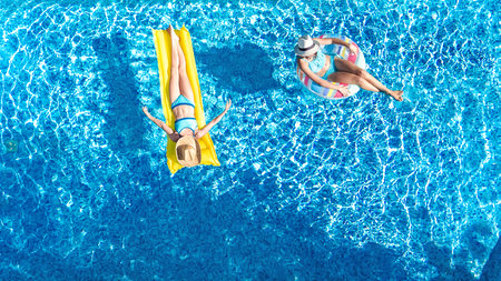 Aerial drone view of children in swimming pool from above, happy kids swim on inflatable ring donuts, girls have fun in water on family vacation