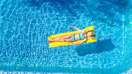 Beautiful young girl relaxing in swimming pool, swims on inflatable mattress and has fun in water on family vacation, tropical holiday resort, aerial drone view from above Reklamní fotografie