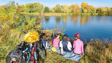 Family on bikes autumn cycling outdoors, active parents and kid on bicycles, aerial view of happy family with child relaxing near beautiful river from above, sport and fitness concept Reklamní fotografie