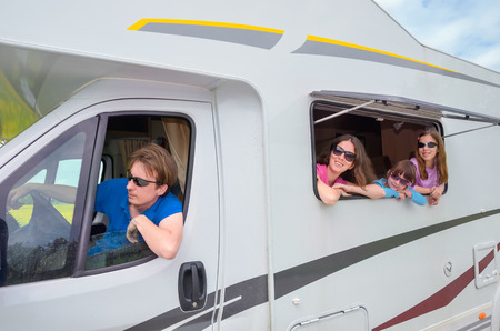 Family vacation, RV travel with kids, happy parents with children have fun on holiday trip in motorhome, caravan camper exterior