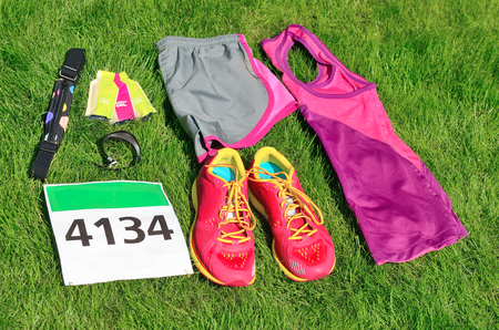 Running shoes, marathon race bib (number), runner gear and energy gels on grass background, sport competition, fitness and healthy lifestyle concept Reklamní fotografie